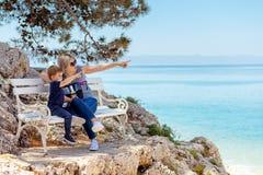 Madre e figlio che si siedono sul banco alla spiaggia rocciosa Immagine Stock