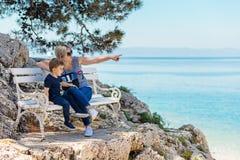 Madre e figlio che si siedono sul banco alla spiaggia rocciosa Immagini Stock