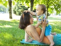 Madre e figlio che si trovano sull'erba immagine stock libera da diritti