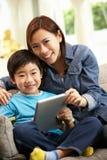 Madre e figlio cinesi che per mezzo del calcolatore del ridurre in pani Immagini Stock Libere da Diritti