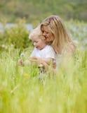 Madre e figlio con il dente di leone in prato Fotografie Stock