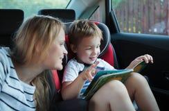 Madre e figlio con un libro nell'automobile Fotografia Stock Libera da Diritti