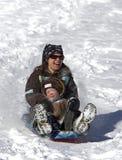 Madre e figlio divertendosi sulla collina della slitta Immagine Stock