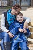 Madre e figlio felici della famiglia sul banco. Immagine Stock Libera da Diritti