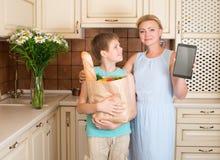 Madre e figlio nella cucina con il sacchetto della spesa di carta pieno della VE immagini stock libere da diritti