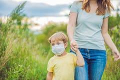Madre e figlio in una maschera medica a causa di un'allergia al ragwee Fotografie Stock Libere da Diritti