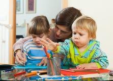 Madre e fratelli germani che giocano con le matite Fotografia Stock Libera da Diritti