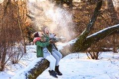 Madre e giovane figlia neve divertentesi, di gioco, di lancio con le mani e ridere in natura di legno di inverno Immagini Stock Libere da Diritti