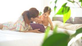 Madre e giovane figlio per trovarsi sul letto e per usare Internet sulla compressa video d archivio
