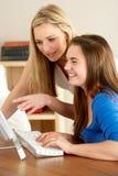 Madre e hija adolescente en el país usando el ordenador Foto de archivo libre de regalías