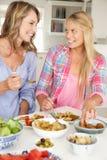 Madre e hija adolescente que disfrutan de la comida Foto de archivo libre de regalías