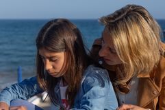 Madre e hija adolescente que hablan por el mar Mediterráneo fotos de archivo libres de regalías