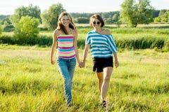 Madre e hija adolescente que llevan a cabo las manos Foto en la naturaleza en día de verano soleado Imágenes de archivo libres de regalías