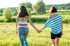 Madre e hija adolescente que llevan a cabo las manos, visión trasera Foto en la naturaleza en un día de verano soleado Fotografía de archivo libre de regalías