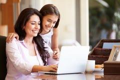 Madre e hija adolescente que miran el ordenador portátil junto Imagen de archivo