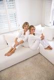 Madre e hija adolescente que se relajan en el sofá blanco Fotos de archivo libres de regalías