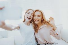 Madre e hija adolescente que toman Selfie en el sofá imágenes de archivo libres de regalías