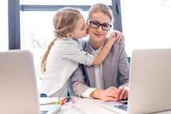 Madre e hija adorable que abrazan y que se besan en oficina con los ordenadores portátiles foto de archivo