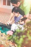 Madre e hija asiáticas con el equipo que cultiva un huerto Effe del vintage Foto de archivo libre de regalías