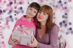 Madre e hija cariñosas con el presente Foto de archivo
