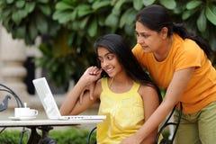 Madre e hija cariñosas con la computadora portátil al aire libre Imágenes de archivo libres de regalías
