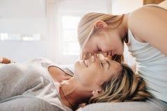 Madre e hija cariñosas en dormitorio Imagen de archivo