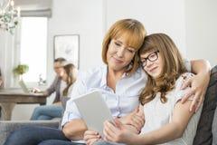 Madre e hija cariñosas que usa la tableta digital con la familia que se sienta en fondo en casa Foto de archivo libre de regalías