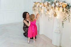 Madre e hija cerca de una decoración de la Navidad Foto de archivo libre de regalías