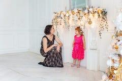 Madre e hija cerca de una decoración de la Navidad Fotos de archivo libres de regalías