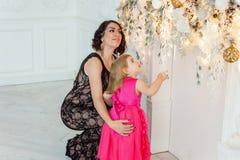 Madre e hija cerca de una decoración de la Navidad Imagenes de archivo