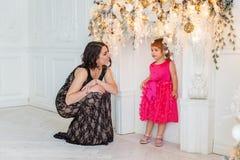 Madre e hija cerca de una decoración de la Navidad Fotografía de archivo libre de regalías