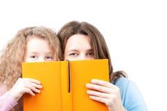 Madre e hija con el libro Fotos de archivo