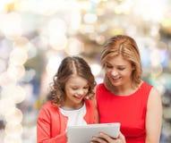 Madre e hija con el ordenador de la PC de la tableta Foto de archivo libre de regalías