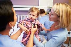 Madre e hija con el personal en Ward Of Hospital pediátrico Foto de archivo libre de regalías