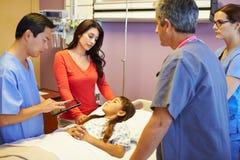 Madre e hija con el personal médico en sitio de hospital Fotos de archivo
