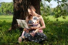 Madre e hija con la computadora portátil imagen de archivo