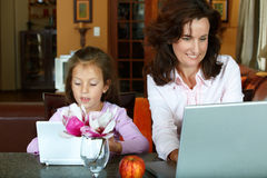 Madre e hija con las computadoras portátiles Imágenes de archivo libres de regalías