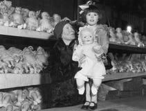 Madre e hija con los estantes de muñecas (todas las personas representadas no son vivas más largo y ningún estado existe Garantía Foto de archivo