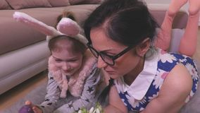 Madre e hija con los huevos de Pascua y los snowdrops en el piso