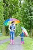Madre e hija con los paraguas Fotos de archivo