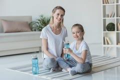 madre e hija con sentarse de las botellas de agua de la aptitud fotografía de archivo