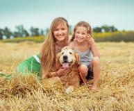 Madre e hija con un perro Foto de archivo