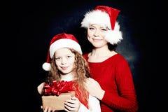 Madre e hija de la Navidad en Santa Hat Having Fun con el regalo Imágenes de archivo libres de regalías