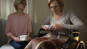 Madre e hija de la silla de ruedas que se sientan junto en la clínica de reposo, visita de ayuda metrajes