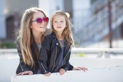Madre e hija de moda vestidas en la calle en la primavera Fotografía de archivo libre de regalías
