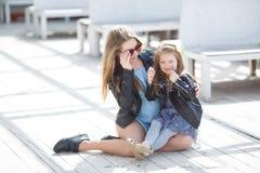 Madre e hija de moda vestidas en la calle en la primavera Foto de archivo libre de regalías