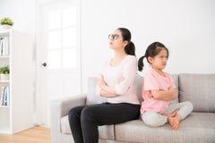 Madre e hija de nuevo a la sentada trasera en el sofá Imagen de archivo libre de regalías