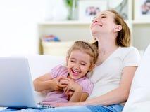 Madre e hija de risa con la computadora portátil Fotografía de archivo libre de regalías