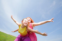 Madre e hija divertidas en hierba verde Imagen de archivo