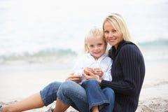 Madre e hija el el día de fiesta que se sienta en la playa Imagen de archivo libre de regalías